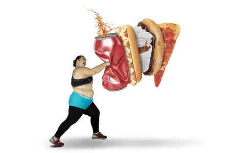 Foto de Diet concept. Overweight woman punching a can of soft drink and junk foods. Isolated on white background - Imagen libre de derechos