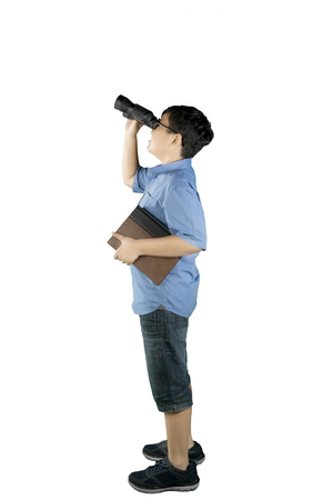 Foto de Portrait of schoolboy looking at something with a binocular while holding a book and standing in the studio - Imagen libre de derechos