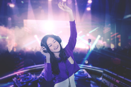 Photo for Image of a young DJ looks happy while playing her song for people in the nightclub - Royalty Free Image