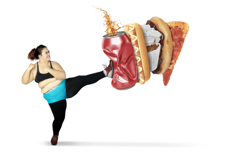 Photo for Diet Concept. Obese woman kicks a can of soft drink and fast foods while wearing sportswear. Isolated on white background - Royalty Free Image