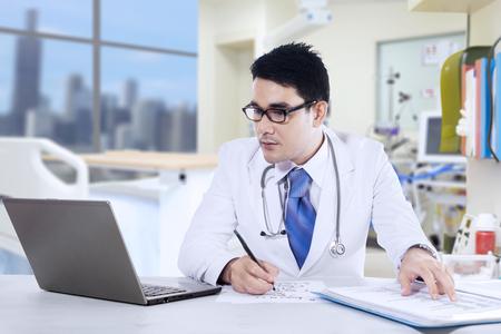 Photo pour Portrait of male doctor is writing a prescription at the clinic - image libre de droit