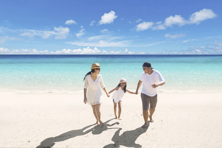 Photo pour Young parents having a holiday with their daughter while walking in the tropical beach - image libre de droit