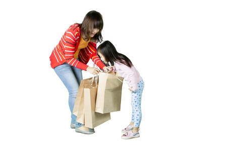 Little girl looking into shopping bags with her mother while standing in the studio, isolated on white background