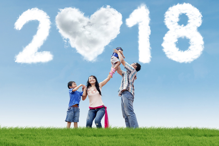 Photo pour Young parents playing with their children in the meadow with clouds shaped numbers 2018 and heart - image libre de droit