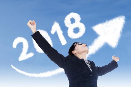 Foto de Image of beautiful businesswoman raising her hands with clouds shaped number 2018 and upward arrow in the sky - Imagen libre de derechos