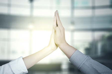 Photo pour Hands of two business people giving high five together with sunlight background - image libre de droit