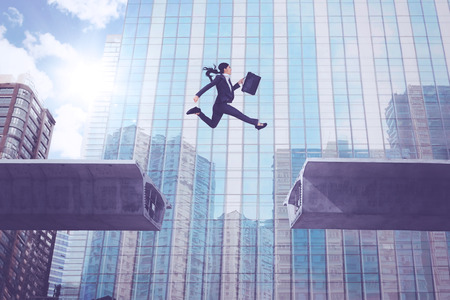 Photo pour Young businesswoman carrying a suitcase while jumping over bridge gap with an office building background - image libre de droit