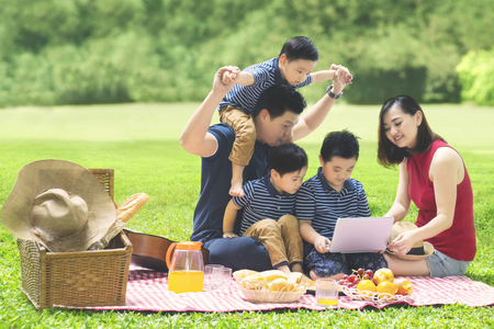 Foto de Image of Asian family using a laptop while enjoying holiday and picnicking in the park - Imagen libre de derechos