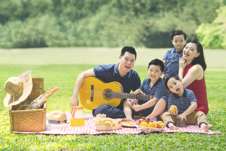 Photo for Image of Chinese family enjoying holiday while picnicking and playing a guitar together in the park - Royalty Free Image