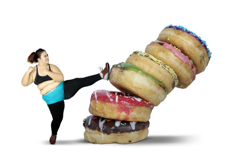Photo for Diet Concept. Obese woman kicking stack of donuts while wearing sportswear. Isolated on white background - Royalty Free Image