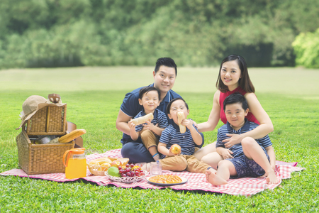 Photo pour Picture of cheerful family smiling at the camera while picnicking together in the park - image libre de droit