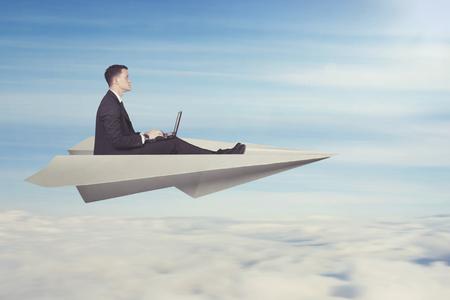 Foto de Businessman with laptop flying on a paper plane - Imagen libre de derechos