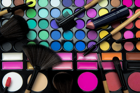 Top view of variety cosmetic brushes with lipstick on the colorful eyeshadow palette