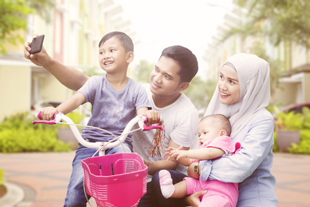Photo for Happy muslim family taking selfie spending quality time in summer - Royalty Free Image