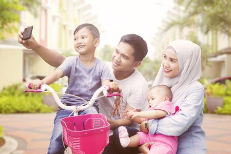 Foto de Happy muslim family taking selfie spending quality time in summer - Imagen libre de derechos