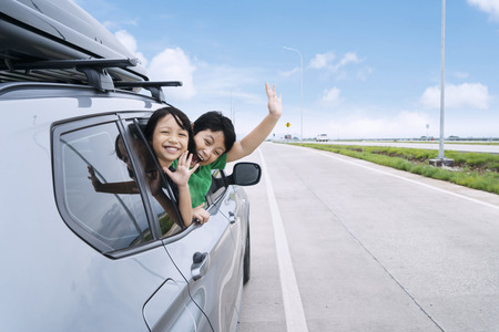 Foto de Happy siblings waving hands travel by car against blue sky. Summer road trip concept - Imagen libre de derechos