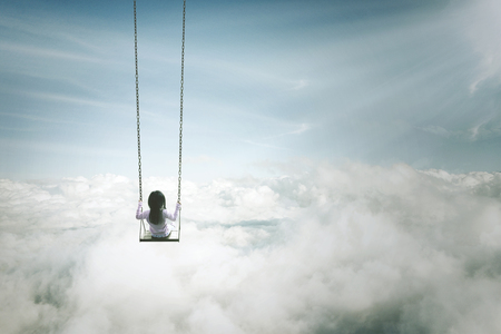 Photo pour Back view of a lonely girl sitting on the swing. Shot above the clouds - image libre de droit