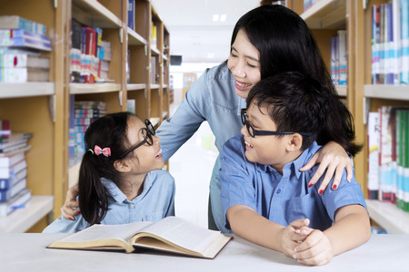 Photo pour Photo of two elementary students talking with their teacher while studying together in the library - image libre de droit