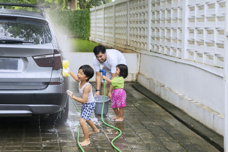 Foto de Picture of two little children helping their father while washing a car together - Imagen libre de derechos