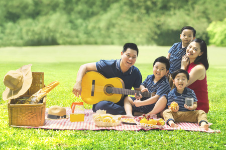 Photo pour Chinese family smiling at the camera while playing a guitar and singing together in the park - image libre de droit