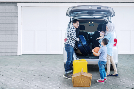 Photo pour Picture of Muslim family preparing suitcase into a car for holiday while standing together in the garage - image libre de droit