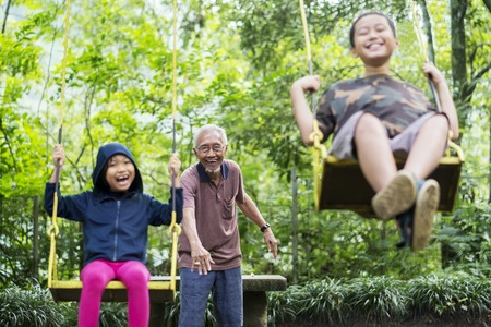 Foto de Picture of two children looks happy while playing with their grandfather in the park - Imagen libre de derechos