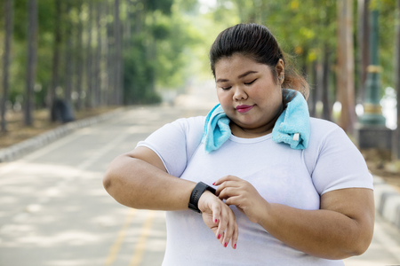 Foto per Picture overweight woman wearing her smartwatch before doing a jogging on the road - Immagine Royalty Free