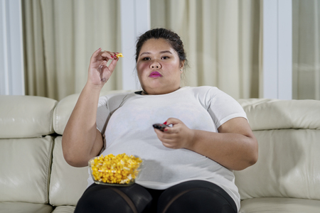 Photo pour Image of obese woman eating popcorn while watching television in the living room - image libre de droit