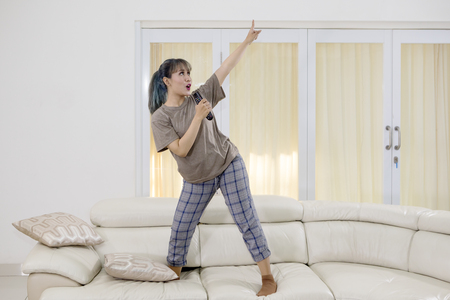 Foto de Young woman singing with a remote control while dancing on the couch. Shot at home - Imagen libre de derechos