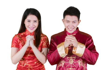 Foto de Picture of happy Chinese couple wearing cheongsam dress while congratulating Chinese new year in the studio - Imagen libre de derechos