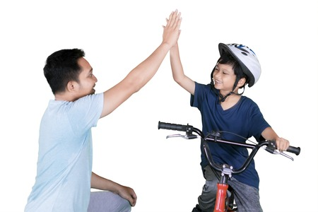 Photo pour Picture of Asian little boy riding bicycle while giving high five hands with his father in the studio - image libre de droit