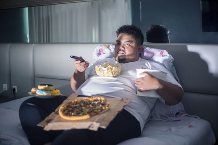 Photo pour Unhealthy lifestyle concept: Asian fat man eating junk foods while watching TV in bed before sleep - image libre de droit