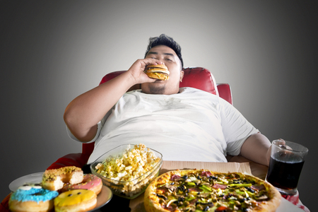 Foto per Image of Asian fat man looks greedy while eating junk foods on the sofa. Shot in the dark room - Immagine Royalty Free