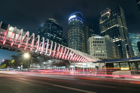 Photo for JAKARTA - Indonesia. March 05, 2019: Beautiful night view of Sudirman street with futuristic pedestrian bridge and light trails - Royalty Free Image