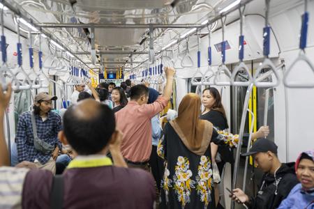 Photo pour JAKARTA, Indonesia - March 27, 2019: Crowd passengers standing inside Jakarta MRT while holding handgrip - image libre de droit