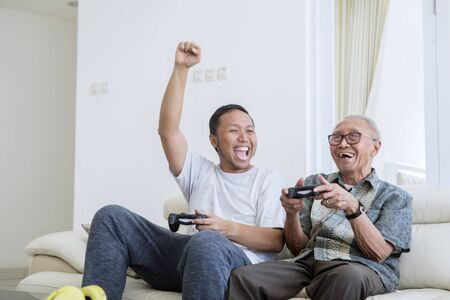 Foto de Excited young man playing video games with his father and sitting on the sofa at home - Imagen libre de derechos