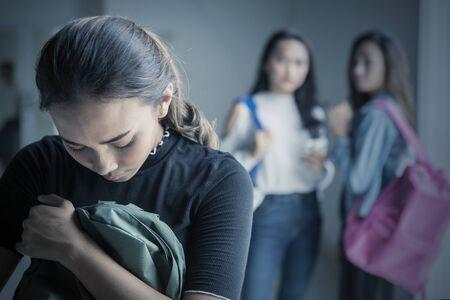Foto de Picture of depressed teenage girl bullied with her friends in the classroom - Imagen libre de derechos