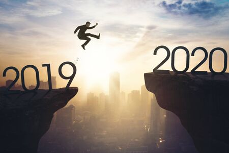 Photo for New year concept. Male manager jumping gap on the cliff from number 2019 to number 2020. Shot at sunrise time - Royalty Free Image