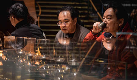 Foto de SHANGHAI, CHINA - JANUARY 11, 2020: Unsprcific man is dringing coffee at the Starbucks Reserve Roastery in Shanghai.The second largest in the world. - Imagen libre de derechos