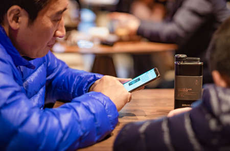 Foto de SHANGHAI, CHINA - JANUARY 11, 2020: Unsprcific man looking at the mobile phone at the Starbucks Reserve Roastery in Shanghai.The second largest in the world. - Imagen libre de derechos