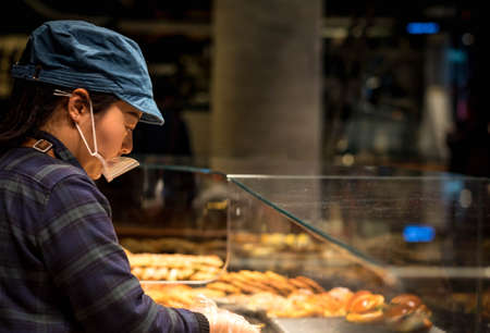 Foto de SHANGHAI, CHINA - JANUARY 11, 2020: Unsprcific employee is doing their work at the Starbucks Reserve Roastery in Shanghai. The second largest in the world. - Imagen libre de derechos