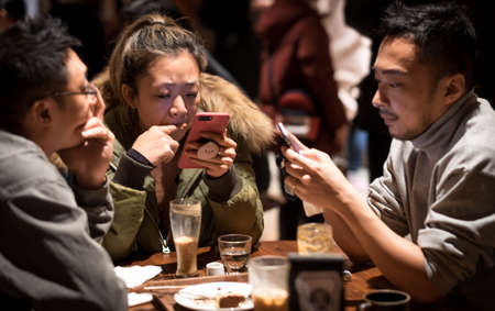 Foto de SHANGHAI, CHINA - JANUARY 11, 2020: Unsprcific people playing the mobile phone at the Starbucks Reserve Roastery in Shanghai. The second largest in the world. - Imagen libre de derechos