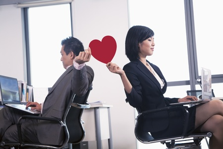 Photo pour Work romance between two business people holding a heart - image libre de droit
