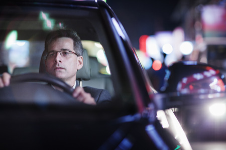 Photo for Businessman driving at night in the city - Royalty Free Image