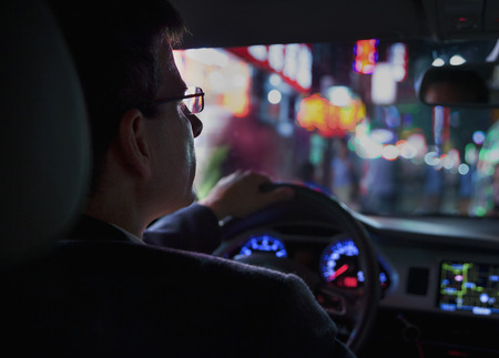 Over the shoulder view of businessman driving at night in the city, illuminated city lights