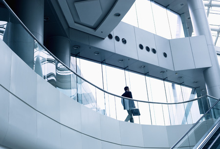 Photo pour Distant businessman walking in a modern office building - image libre de droit