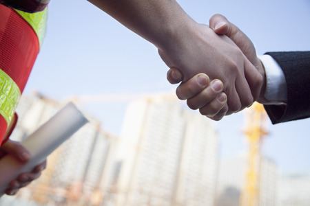 Close up of architect and building contractor shaking hands