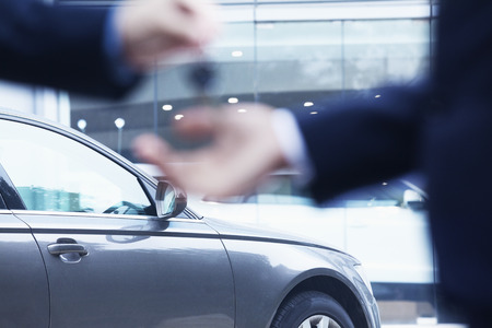 Photo pour Car salesman handing over the keys for a new car to a young businessman, close-up  - image libre de droit