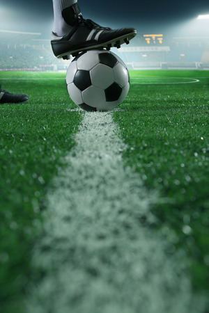 Foto de Close up of foot on top of soccer ball on the line, side view, stadium - Imagen libre de derechos