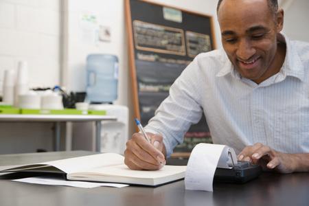 Photo pour Man doing accounts in cafe - image libre de droit